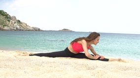 Young sporty female does stretching exercise on the beach near the sea. Healthy active lifestyle concept. stock video