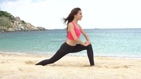 Young sporty female does stretching exercise and sit on twine split on the beach near the sea stock footage