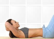 A young and sporty female is doing abs exercise Stock Images
