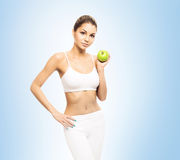 Young, sporty, fit and beautiful girl with the apple isolated on Stock Photography