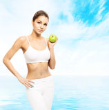Young, sporty, fit and beautiful girl with an apple Royalty Free Stock Image