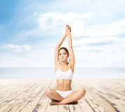 Young, sporty, fit and beautiful girl meditating isolated on whi Stock Photo