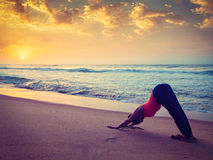 Young sporty fit woman doing yoga at beach on sunset Royalty Free Stock Photos