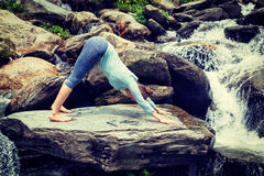 Young sporty fit woman doing yoga oudoors at tropical waterfall Royalty Free Stock Image