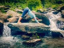 Young sporty fit woman doing yoga oudoors at tropical waterfall Royalty Free Stock Images