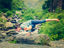 Young sporty fit woman doing yoga oudoors at tropical waterfall Stock Photos