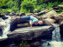 Young sporty fit woman doing yoga oudoors at tropical waterfall Royalty Free Stock Photo