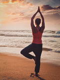 Young sporty fit woman doing yoga tree asana on beach Royalty Free Stock Photography