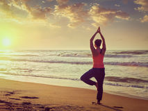 Young sporty fit woman doing yoga tree asana on beach Stock Images