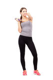 Young sporty fitness woman holding dumbbell pointing at you. Stock Photo
