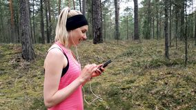 Sporty fitness woman using smart phone after workout in forest stock footage