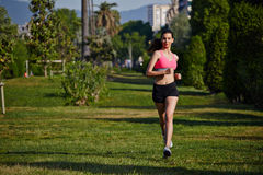 Young sporty girl in bright sportswear running in the park on beautiful trees background. Fitness and healthily lifestyle, sport and healthy concept, jogging and royalty free stock images