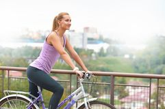 Young sporty girl cycling at city stock photos