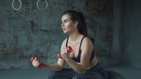Young girl in red sportswear doing exercise with dumbbells on the background of a brick wall. Young sporty girl doing exercise with dumbbells on the background stock video footage