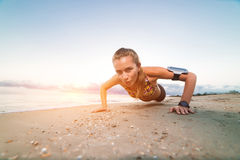 Young sporty girl doing push ups on beach at sunrise royalty free stock images