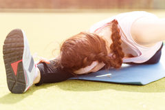 Young sporty girl doing stretching on fitness mat Royalty Free Stock Images