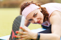 Young sporty girl doing stretching on fitness mat Stock Photography