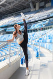 Young sporty girl doing workout at the stadium. She raised her leg up over my head. Woman in sportswear a great stretch Stock Image