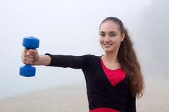 Young sporty girl exercising with dumbells during fitness workou Royalty Free Stock Photo