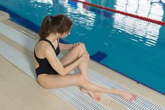Young sporty girl feeling pain in her foot at swimming pool. Stock Image