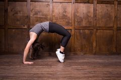 Fitness and exercice concept. Young sporty girl in gym. Making bridges exercise Stock Photos