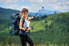 Sporty woman hiker with backpack and trekking sticks hiking in the mountains. Young sporty girl hiker with backpack standing on the top of a hill, pointing away Stock Image