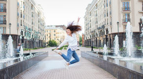 Young sporty girl jumping for joy at the fountain in the residential complex. Female in flight with his hands up.  stock image