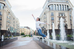 Young sporty girl jumping for joy at the fountain in the residential complex. Female in flight with his hands up.  stock photography