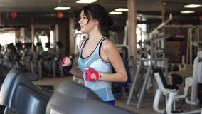 Young sporty girl running on the treadmill at the gym. fitness, sports, health. Girl running on the treadmill in the fitness room. young woman doing aerobic stock video