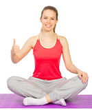 Young sporty girl sits is lotus pose Stock Photos