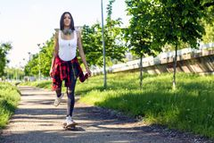Young sporty girl on skateboards skate on the street royalty free stock image