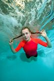 Young sporty girl is swimming underwater on a blue background in a red bathing suit, looking at me and smiling. Bottom view from under the water. Portrait Royalty Free Stock Photos