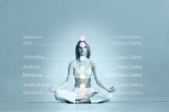 Young and sporty girl training in gym. Yoga exercise. Young and healthy girl meditating in lotus position. Colored chakra lights over her body. Yoga, zen Stock Image