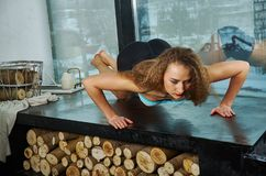 Young sporty girl warming up and doing some push ups. Sporty female blonde girl warming up and doing some push ups big window on background royalty free stock photos