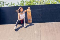 Young sporty girl holding skateboard Outdoors, urban lifestyle royalty free stock photos