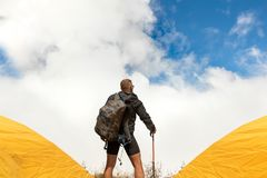 Young sporty guy with a backpack in a tent camp looking afar against a background of cumulus clouds and a blue sky. Travel concept Stock Photos