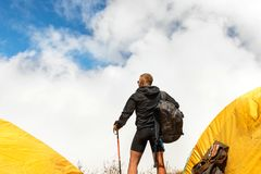 Young sporty guy with a backpack in a tent camp looking afar against a background of cumulus clouds and a blue sky. Young sporty guy with a backpack in a tent Royalty Free Stock Photos