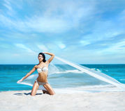 Young, sporty and happy woman posing with blowing silk Royalty Free Stock Image