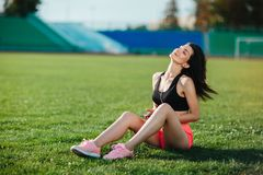 Young sporty joyful woman brunette in sport dress sitting on the grass football field stadium and listens to music in earphones, h royalty free stock photo