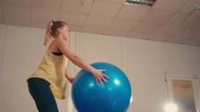 Young Sporty Lady is Doing Squats with Fitball at Hands in Training Gym. Young Sporty Lady is Exercising by Doing Squats with Fitball at Hands in Training Gym stock footage