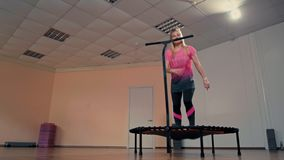 Sporty woman is jumping very high on trampoline at fitness training in the gym. Young sporty lady is jumping very high on mini trampoline during fitness training stock footage