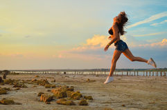 Young sporty lady in shorts and trainers jogging Stock Photography