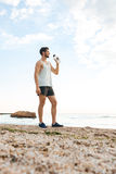 Young sporty man athlete resting after jogging and drinking water Stock Photography