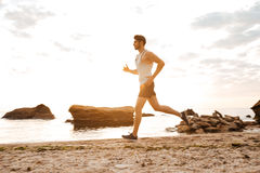 Young sporty man athlete running at the rocky beach Royalty Free Stock Photo