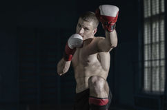 Young sporty man. Young athletic man with boxing gloves and a rack Stock Photo