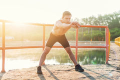 Young sporty man bending forward and doing stretching exercise. Young sporty man bending forward and doing stretching exercise Royalty Free Stock Photo