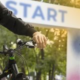 A young sporty man on the bicycle on the start point of the cycling race. Start text. Bokeh background. Square image royalty free stock photo
