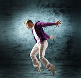 A young and sporty man doing a modern dance pose. A young and sporty Caucasian man in attractive clothes doing a modern dance pose. The image is taken on a royalty free stock images