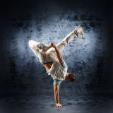 A young and sporty man doing a modern dance pose. A young and sporty Caucasian man in attractive clothes doing a modern dance pose. The image is taken on a royalty free stock photos