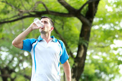 Young sporty man drinking mineral water Royalty Free Stock Photos